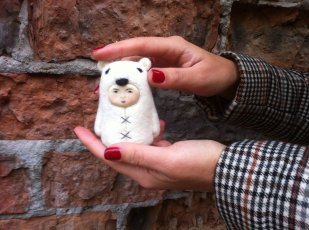 Tiny handmade felt doll that looks like a bear.