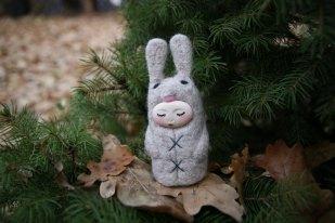 Tiny handmade felt doll that looks like a bunny.