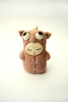 Tiny handmade felt doll that looks like a sleepy dragon.