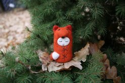 Tiny handmade felt doll that looks like a fox.