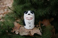 Tiny handmade felt doll that looks like a panda.
