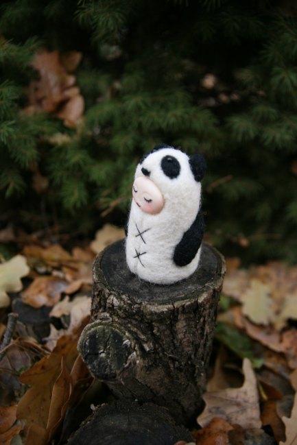 Tiny handmade felt doll that looks like a panda.