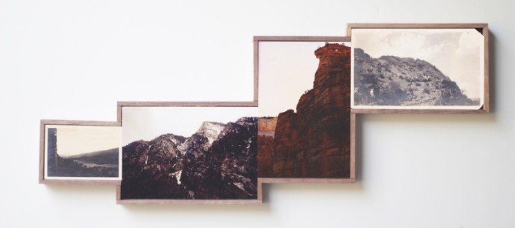 Picture of four framed vintage landscape photos on the wall.