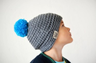 Little boy portrait wearing a grey and blue hat with pom pom.