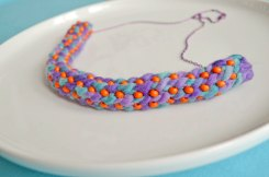 Closeup of a purple, orange and light blue crocheted necklace.