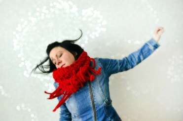 Woman wearing a bright red crocheted scarf.