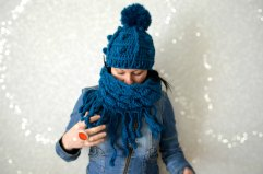 Woman wearing a crocheted blue hat and scarf