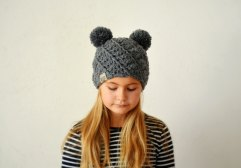 Girl portrait with closed eyes wearing a grey double pom pom hat.