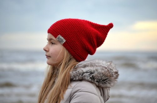 Girl wearing a bright red hat in outdoor.