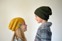 Kids wearing a yellow and green crocheted hat.