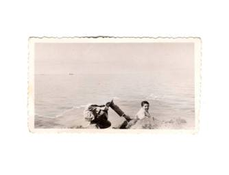 Picture of an handmade collage of a teared vintage photo of a man and a kid at the beach.