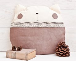 Still life photo of a brown cat shaped pillow with a book and some pine cones.