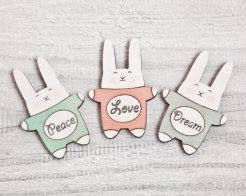 Still life photo of three bunny shaped fridge magnets colored with pastel colors.
