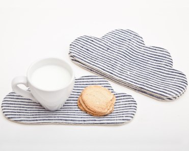 Still life photo of 2 striped coasters with a cloud shape, and a white cup with milk and biscuits on a side.