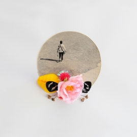Paper cut in circle decorated with colorful mixed media materials.