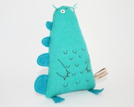 Still life of a turquoise soft toy that looks like a dinosaur.