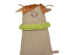 Still life photo of a cow soft toy wearing a green scarf.