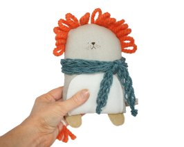 Still life picture of a lion soft toy with a blue scarf.
