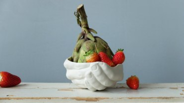 Still life photo of a sculpture bowl with strawberries and an artichoke plant.