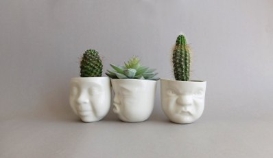Still life picture of the planters that have funny faces sculptured on the front.