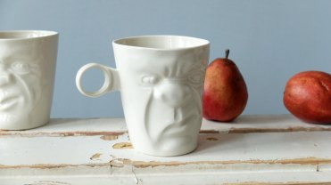Still life of a white ceramic mug that have a face sculptured in the front.
