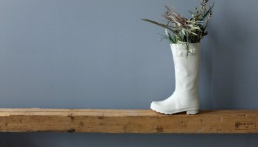 Still life photo of a ceramica vase that looks like a boot.