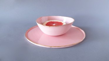 Still life photo of two pastel pink plates with a red orange.