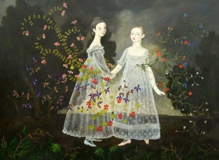 Full body portrait of a couple of girls surrounded of flowers and with a natural landscape on their back.