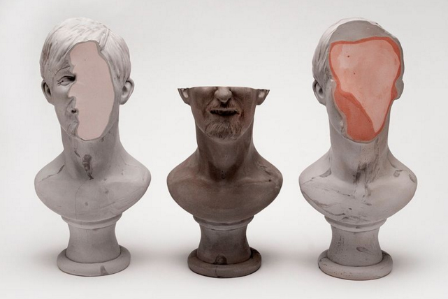 Photo of three defaced busts.