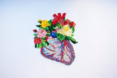 Still life photo of a beaded heart Necklace seen from above.