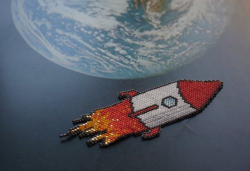 Still life photo of a beaded rocket ship necklace with a reproduction of the Hearth as a background.