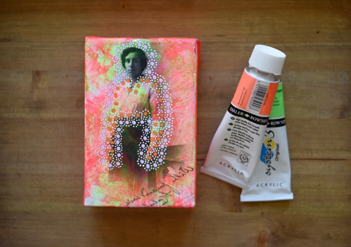 Still life photo of a collage on canvas of a vintage portrait with two acrylics fluorescent colours aside.
