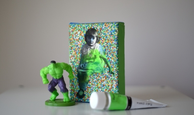 Still life picture of a baby girl portrait on canvas with a little Hulk action figure and an acrylic colour aside.