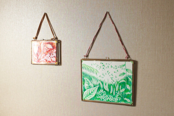 Still life photo of two framed illustrations hang on a wall.