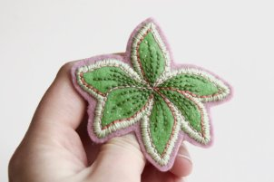 Still life photo of a close up of an hand holding an stitched handmade brooch.