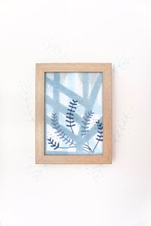 Still life photo of a framed abstract textile art with geometric forms, frontal view.