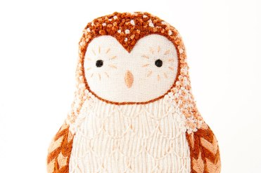Still life photo of an owl plush toy, frontal view.