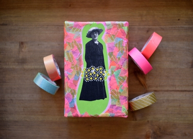Still life of a canvas about a vintage woman portrait with some washi tape rolls aside.