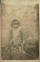 Vintage photo of a baby girl portrait staring at the camera sewed with a white thread.