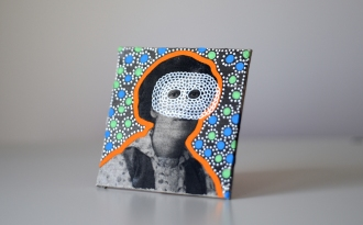 Still life of a collage on canvas of a vintage masked woman portrait decorated with pens.