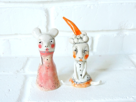 Still life photo of two ceramics sculptures decorated with pink and orange and surrounded by a white background.