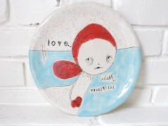 Still life photo of a ceramic plate decorated with an illustration coloured in red and light blue.