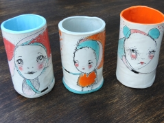 Still life photo of three ceramic cups decorated with bright colours and illustrations.