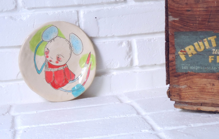 Still life photo of a ceramic plate decorated with a coloured illustration.