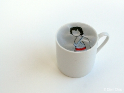 Still life of a porcelain cup with an illustration of a woman inside realised with thread.