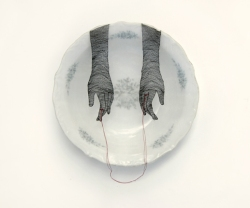 Still life of a porcelain plate seen from above with an illustration draw on of two hands holding a red thread.