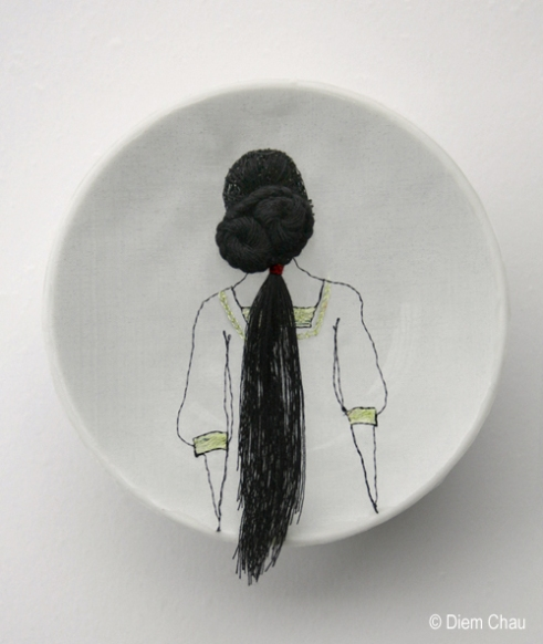 Still life of a porcelain bowl seen from above with an illustration of a girl seen from her back with long hair.