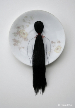 Still life photo of a porcelain plate seen from above with an illustration of a girl seen from her back with long hair.