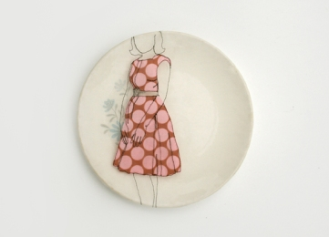 Still life of a porcelain plate seen from above with an illustration of a girl with a dotted dress.