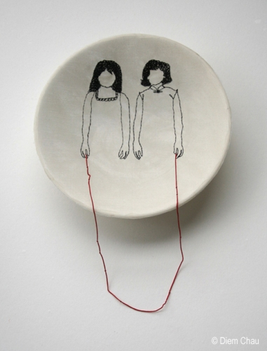 Still life of a porcelain bowl seen from above with an illustration of two young girls holding a red thread.